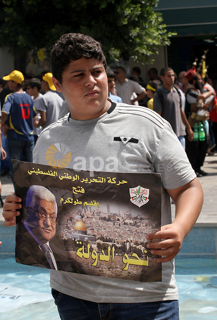 A Palestinian Fatah supporter holds a picture of Palestinian President Mahmoud Abbas during a protest marking the 48th anniversary of the Sabra and Shatila massacre in 1982, in the West Bank city of Nablus, September 16, 2014. The Sabra and Shatila massacre was the slaughter of between 762 and 3,500 civilians, mostly Palestinians and Lebanese Shiites, by the Kataeb Party, a Lebanese Christian militia, in the Sabra neighborhood and the adjacent Shatila refugee camp in Beirut, Lebanon. On 15 September, 63 Palestinian were individually identified and killed by an Israeli unit called Sayeret Matkal, and on 18 September 1982 a more widespread massacre was carried out by a Lebanese Christian Phalangist militia. Photo by Nedal Eshtayah