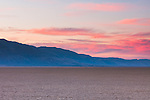 Magenta and purple clouds are lit by the setting sun over distant hills seen from the Alvord Desert in Southeast Oregon.