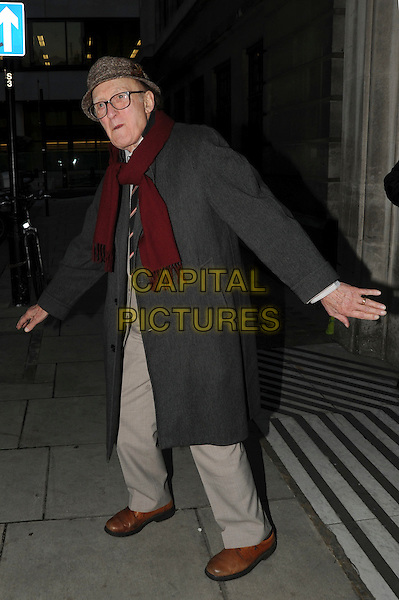 RON MOODY.Leaving BBC Radio 2, London, England..November 15th, 2010.full length grey gray trousers coat scarf red hat glasses hands arms.CAP/IA.©Ian Allis/Capital Pictures.