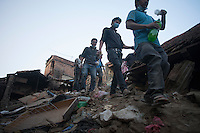 Nepali rescue workers walks on collapsed houses at Vaktapur, outstrike of Kathmandu, Nepal. May 1, 2015