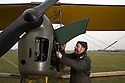 """13/03/15<br /> <br /> Colin Temple-Smith prepares the restored Tiger Moth for its first flight.<br /> <br /> ***FULL STORY HERE:   http://www.fstoppress.com/articles/tiger-moth-restorations/    ****<br /> <br /> You may remember spending hours toiling over Airfix models, painstakingly following intricate instructions and trying not to glue your fingers together before painting your own miniature version of one of the RAF's or Luftwaffe's finest aircraft. Then spare a thought for one man who has just helped to restore and put together one World War Two Tiger Moth and is about to start piecing together another FOUR aircraft that were discovered in bits in a barn.<br /> <br /> Sixty-year-old Colin Temple-Smith – who wears a moustache that any Wing Commander would be proud of – has spent a lifetime restoring vintage cars and motorcycles and recently quit his job as a window fitter to help re-build the five bi-planes that will become part of a growing fleet of Tiger Moths at Derbyshire based Blue Eye Aviation.<br /> <br /> Today saw the first of the fully-restored five aircraft take to the skies.<br /> <br /> """"It's just like working on old bikes and cars, although they're a lot more fragile"""" explained Colin, whose wife runs the Aviators Café at Darley Moor Airfield near Ashbourne.<br /> <br /> """"When I was a teenager I used to be a member of a modelling club, making flying models from wood and canvas. They're very similar to build – it's really just the size that's changed with these.<br /> <br /> All Rights Reserved: F Stop Press Ltd. +44(0)1335 418629   www.fstoppress.com."""
