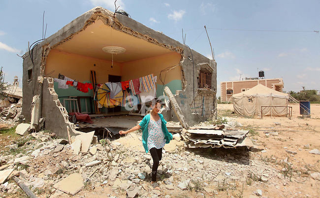 A Palestinian girl walk in front of the ruins of her family house, that witnesses said was destroyed by Israeli shelling during a 50-day war last summer, in Khan Younis in the southern Gaza Strip July 2, 2015. Robert Turner has no quick and easy answer when asked to name the worst of times in his three years running the United Nations' relief effort in Gaza. Photo by Ashraf Amra