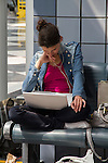 Denver International Airport terminal and woman using laptop, Denver, Colorado .  John leads private photo tours in Boulder and throughout Colorado. Year-round Colorado photo tours. .  John offers private photo tours in Denver, Boulder and throughout Colorado. Year-round Colorado photo tours.