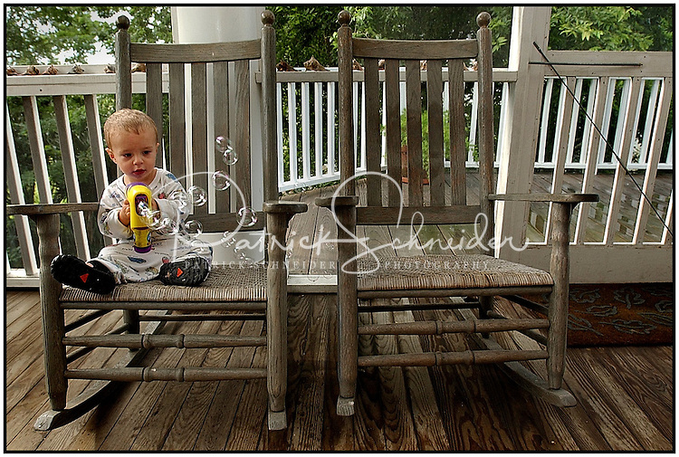 A young boy blows bubbles using a bubble-making gun as he sits lone on a porch with old rocking chairs.  Model released image may be used to illustrate other destinations or concepts.