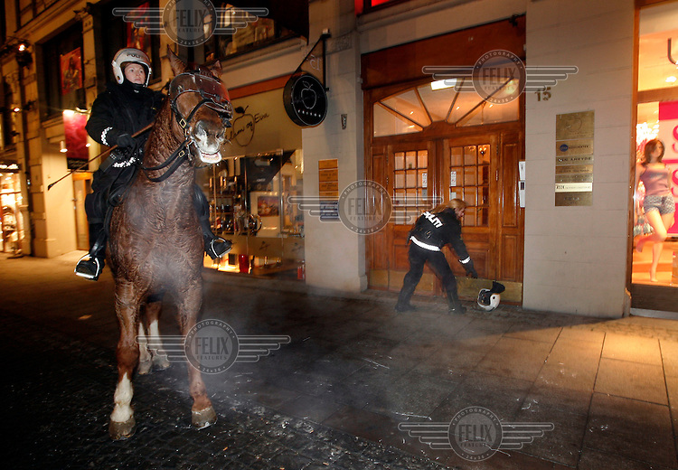 A police woman picks up her helmet after being thrown from her horse, after a mob fired at the horsed with fireworks. Pro-Palestinian protesters clashed with police as they held another demonstration against Israel in the Norwegian capital Oslo. Violent clashes lasted for hours  in the centre of Oslo. Israeli forces began a series of air strikes on the Gaza Strip on the 27th of December in retaliation against Hamas rockets fired into Israel. After eight days of bombardment, leaving over 400 Palestinians and four Israelis dead, Israeli tanks launched a ground invasion on the 4th of January.