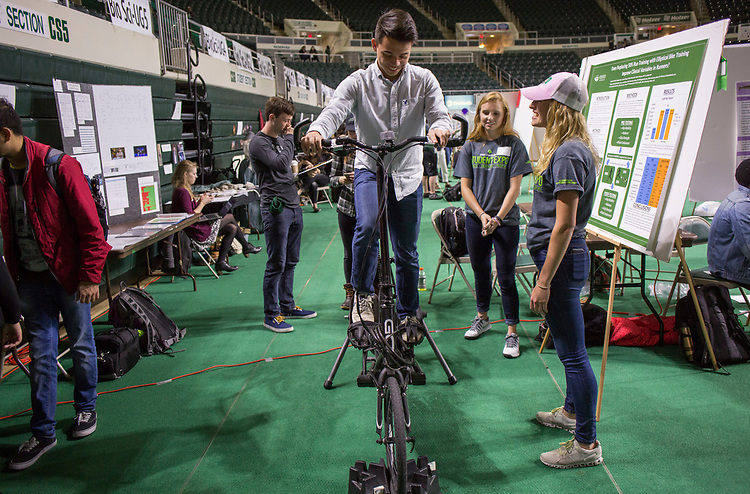 Caedon Ly, a junior at Logan High School, tries out an elliptical bike at the student expo on April 6, 2017.