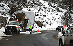 A Caltrans worker directs traffic around a large boulder in the road on Highway 88 near Sorensons Resort on Tuesday, Dec. 21, 2010. The boulder, which was dislodged by a series of wet storms that battered the region over the weekend, is expected to be removed Wednesday..Photo by Cathleen Allison