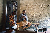 MPHANDULA, MALAWI - AUGUST 21: Ethel Dailesi, age 44, walks out of her bedroom as her daughter Rebecca Masawo, age 10, plays cards on August 21, 2006 in Mphandula village, about 30 miles outside Lilongwe, Malawi. Ethel was diagnosed with HIV/Aids in 2004 and has been on antiretroviral drugs since December 2005. She has just taken her medicine. She is often sick and her two daughters take care of her. Her children cook and clean for her. The girls attend a school nearby but they usually stay home when their mother is too sick. Mphandula is a poor village in Malawi, without electricity or clean water. Nobody owns a car or a mobile phone. Most people live on farming. About 7000 people reside in the village and the chief estimates that there are about five-hundred orphans. Many have been affected by HIV/Aids and many of the children are orphaned. A foundation started by Madonna has decided to build an orphan center in the village through Consol Homes, a Malawi based organization. Raising Malawi is investing about 3 million dollars in the project and Madonna is scheduled to visit the village in October 2006. Malawi is a small landlocked country in Southern Africa without any natural resources. Many people are affected by the Aids epidemic. Malawi is one of the poorest countries in the world and has about 1 million orphaned children. (Photo by Per-Anders Pettersson)