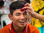 10 JANUARY 2015 - BANGKOK, THAILAND: A Thai teenager gets zombie makeup applied to his face during Children's Day at Government House in Bangkok. National Children's Day falls on the second Saturday of the year. Thai government agencies sponsor child friendly events and the military usually opens army bases to children, who come to play on tanks and artillery pieces. This year Thai Prime Minister General Prayuth Chan-ocha, hosted several events at Government House, the Prime Minister's office.    PHOTO BY JACK KURTZ