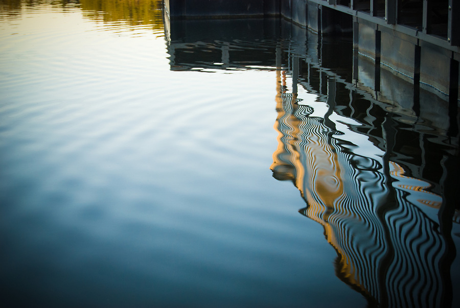 Reflection of dock railing on calm ripples in a blue lake.