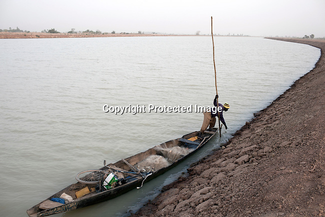TANGAKA, MALI - FEBRUARY 24: A fisherman on his boat on a channel that was built by Chinese for a Libyan company who leases land from the Mali government on February 24 2011, outside Tangaka, Mali. Many farmers in the are were asked to leave the land to make place for the new big scale farming to take place. Photo by Per-Anders Pettersson