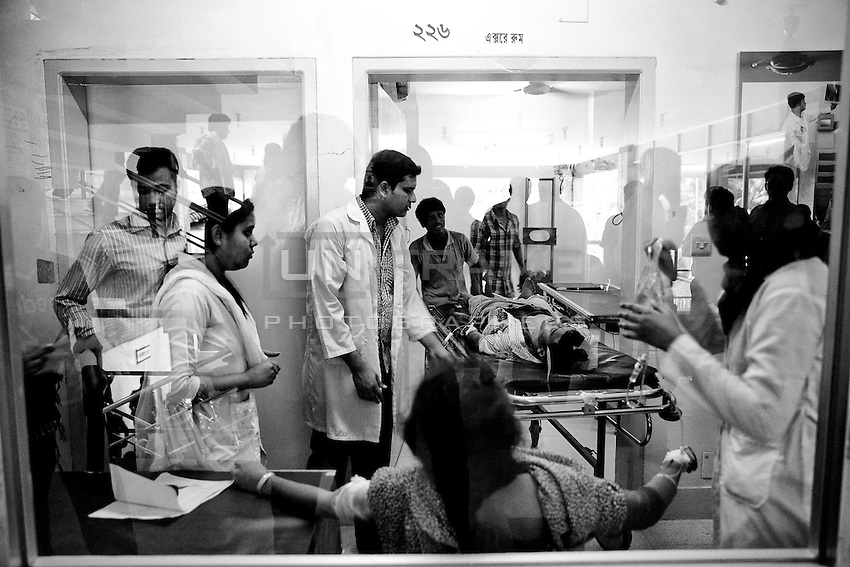 Doctors of Anam Medical College Hospital take a victim of Rana Plaza building collapse to hospital as part of its medical service during the rescue operation at the site of Savar tragedy.  Savar, near Dhaka, Bangladesh