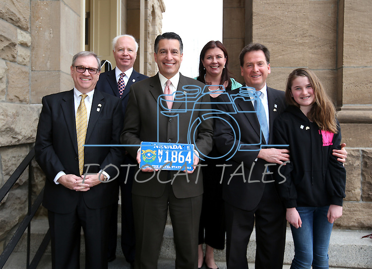 Back row, from left, Nevada Museums and History Director Peter Barton and NV150 Executive Director Kara Kelly; front row, from left, Wells Fargo Regional President Kirk V. Clausen, Gov. Brian Sandoval, Lt. Gov. Brian Krolicki and his daughter Ellie pose for photos after a ceremony marking the beginning of production of the second design in a four-part series of Sesquicentennial medallions at the Nevada State Museum, in Carson City, Nev., on Wednesday, Feb. 26, 2014. <br /> Photo by Cathleen Allison/Nevada Photo Source