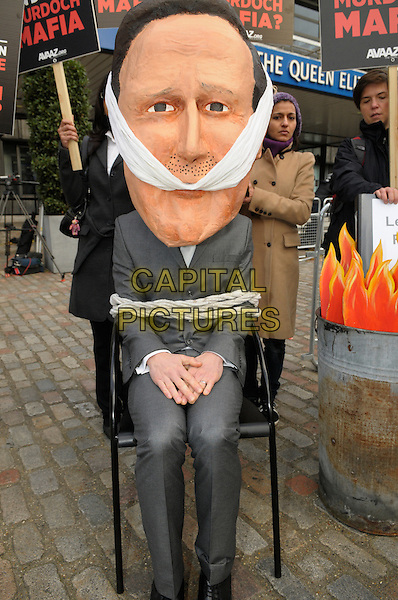 David Cameron Effigy.Members of the 'Hacked Off' campaign group address the media outside the Queen Elizabeth II conference centre following the publishing of the Leveson Inquiry, London, England,.November 29th 2012..full length bound gagged placards david cameron slogan protest demonstration protesting ropes grey gray suit head  .CAP/IA.©Ian Allis/Capital Pictures.