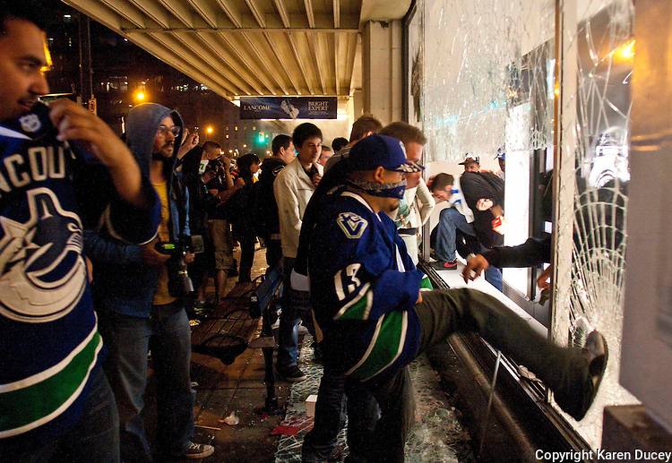 Rioters break windows of department store, Hudson's Bay Company, on the downtown streets of Vancouver,BC on June 15, 2011. (photo copyright Karen Ducey)