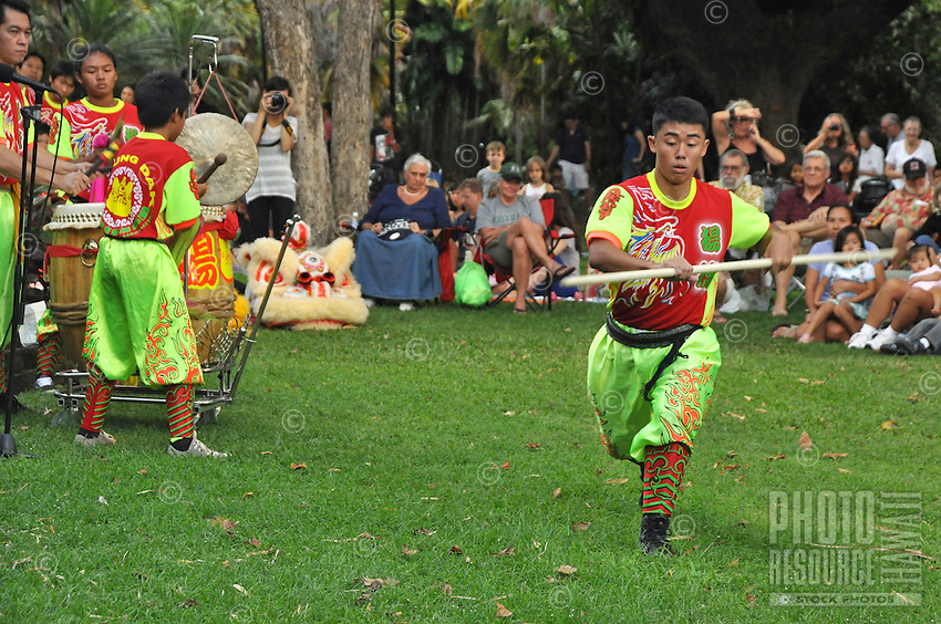 A martial arts performance or demonstration accompanied by drumming at Foster Botanical Garden, Honolulu, O'ahu.