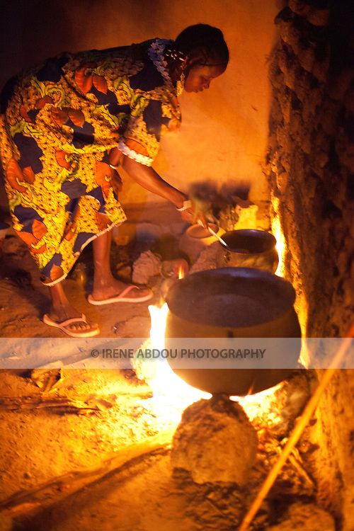 "A woman in Djibo, Burkina Faso cooks millet ""pot,"" similar to the Italian polenta.  Without a stove or electricity, women throughout West Africa cook outside on open fires."