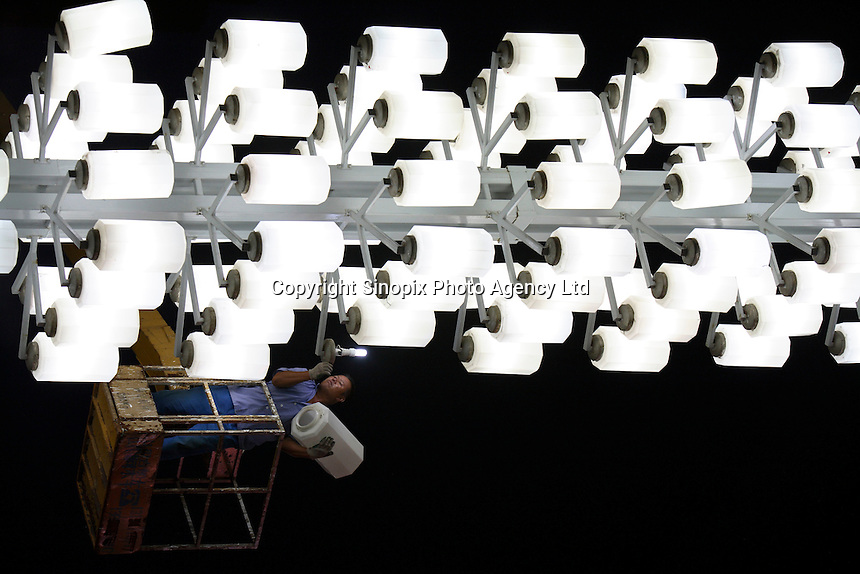 A worker replaces a burned out light bulb in front of the Dalian World Expo Plaza, site of the the World Economic Forum's Inaugural Annual Meeting of the New Champions in Dalian, China..