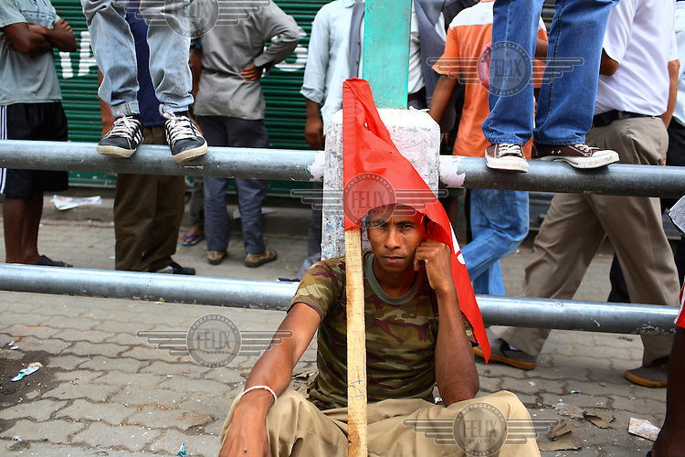A protester sits on the ground holding a flag at a strike called by the Unified Communist Party of Nepal (UCPN) to remove the ruling government. The Maoist opposition blocked streets leading to key government offices on the 6th May, the fifth day of their crippling general strike to demand the prime minister's resignation, but the government has vowed not to bow to the protesters' pressure. The Maoists, known to use violence to back their strike calls, have demanded that residents halt all travel and keep businesses and schools closed since Sunday in their campaign to get Prime Minister Madhav Kumar Nepal to resign and hand power to a Maoist-led government. The strike has shut down most businesses, schools and transport, with daily activity grinding to a standstill.