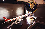 "Interior of John Travolta's jumbo jet. Model jet and globe..John Travolta is pilot of his very own jumbo jet, a 1964 Boeing 707-100 series. In 2003, John Travolta flew his jumbo jet around the world, in partnership with Quantas, to rekindle confidence in commercial aviation, and to remind us that elegance and style are a part of flying. The crew are dressed in tailor made authentic uniforms from the Quantas museum. The men's uniforms are styled on British Naval uniforms and the ladies' designed by Chanel. His jumbo jet sports a personalised number plate N707JT which speaks for itself. The aircraft is named ""Jett Clipper Ella"" dedicated to his son and daughter. This jumbo together with his other aircraft are housed in purpose built hangars at his home in Florida, USA."