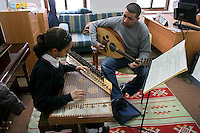 """FOR FAOIROUZ SONG """"THE FLOWER OF THE CITIES"""" - A Palestinian girl plays the Kanoun  and her teacher the Oud during a lesson in the Edward Said National Conservatory of Music in East Jerusalem. Photo by Quique Kierszenbaum."""