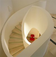 The shell-shaped spiral staircase has marble steps with uprisers covered in mirror