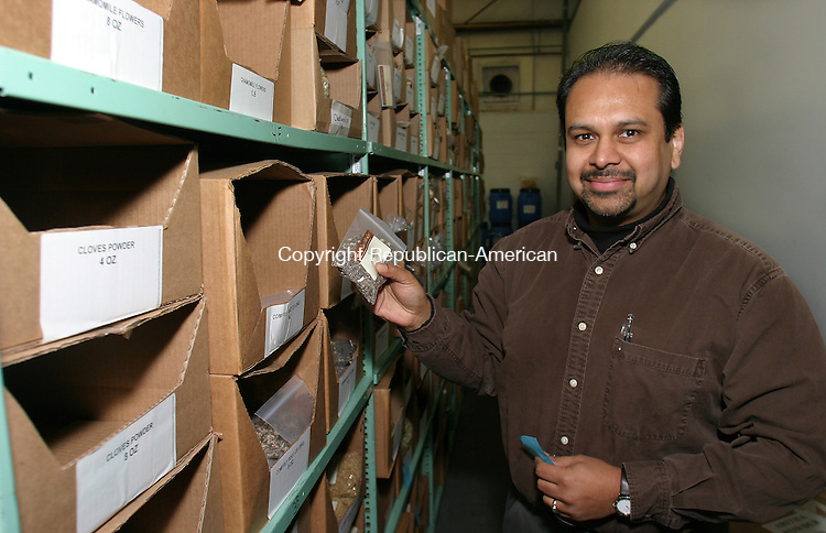 OXFORD, CT. 14 December  2004--121404SV03--Jay Basu, owner of From Nature with Love, stands with some of the prepackaged stock at his business in Oxford Tuesday. His company acquires and distributes natural products used in cosmetics.  Steven Valenti Photo<br />