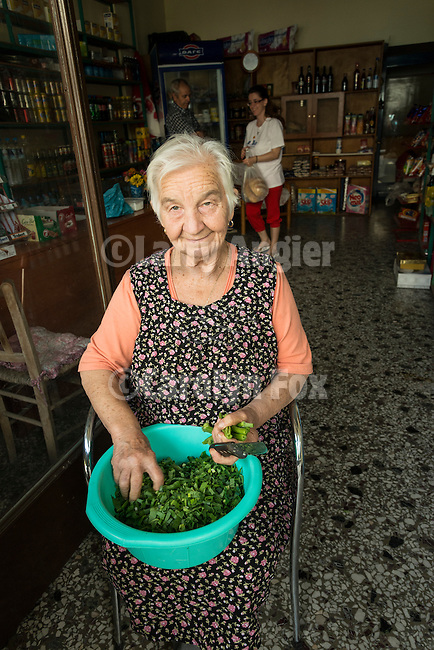 A woman prepares her fava beans in front of her small road-side store in Kastraki, Greece