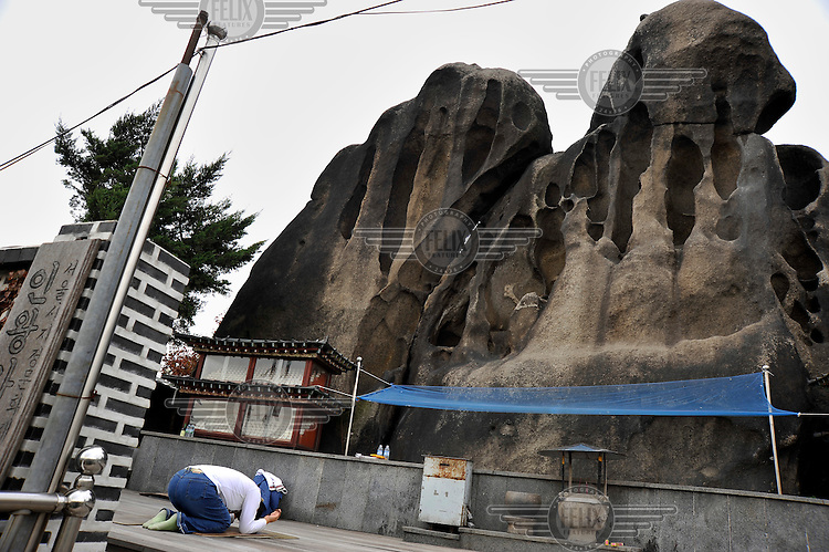 People stand on the Shamanistic rock formations and shrines in the Guksadong district on the outskirts of Seoul, where it is common for people to come to worship and leave offerings.