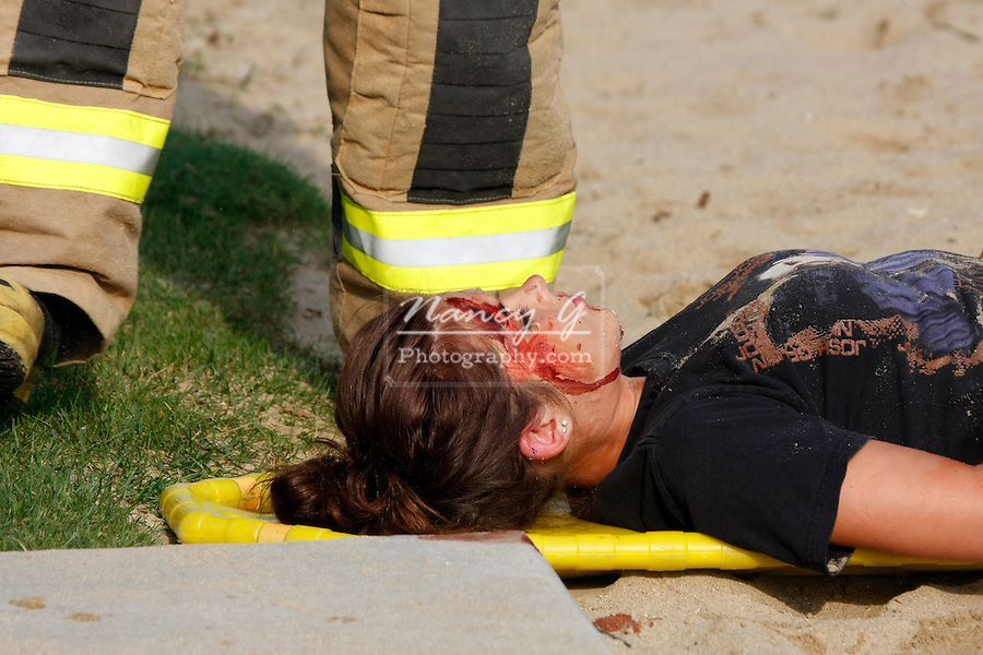 A young injured girl hurt on concrete next to a beach
