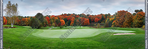 Golf course, beautiful panoramic fall nature scenery at dawn, putting green and sand trap. Muskoka, Ontario, Canada.