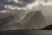 Dramatic autumn light shines over Narvtind mountain peak, Moskenesøy, Lofoten Islands, Norway