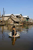 CHILD IN A TUB on the Tonle Sap, her water transportation in getting from one house to the other in the Water Village, Siam Reap Cambodia
