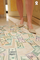 Woman's legs standing on money, in corridor (Licence this image exclusively with Getty: http://www.gettyimages.com/detail/88091092 )