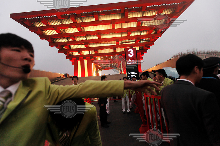 Police officers and security personnel try to keep order as visitors queue to enter the China Pavilion during the first day of the trial run for the 2010 World Expo.