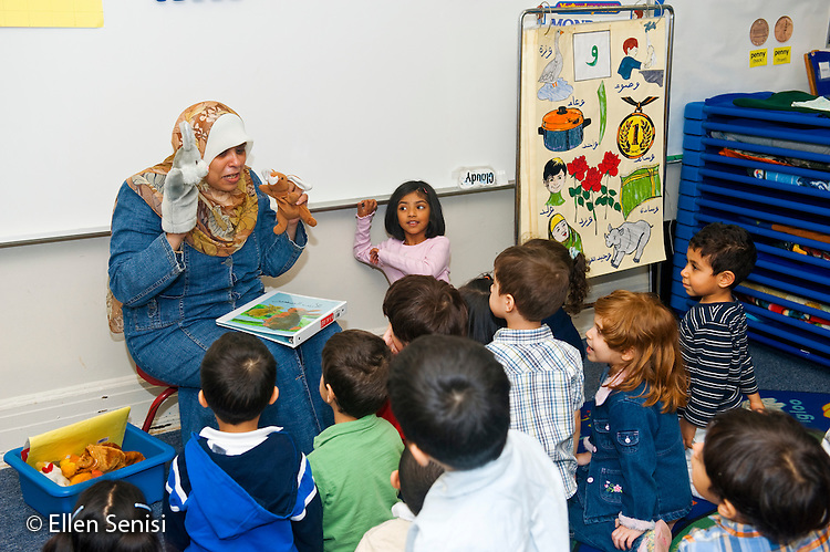 MR / Jersey City, NJ.Al-Ghazaly Elementary School (private Islamic school with a curriculum that follows state curriculum content standards and also teaches Islamic studies) / Pre-K classroom.Arabic language teacher  (Egyptian-American, wearing hajib) tells her students an animated story during an Arabic lesson using hand puppets and facial expressions..ID: AI_gPag  MR: AI_gPag; Bor1.© Ellen B. Senisi