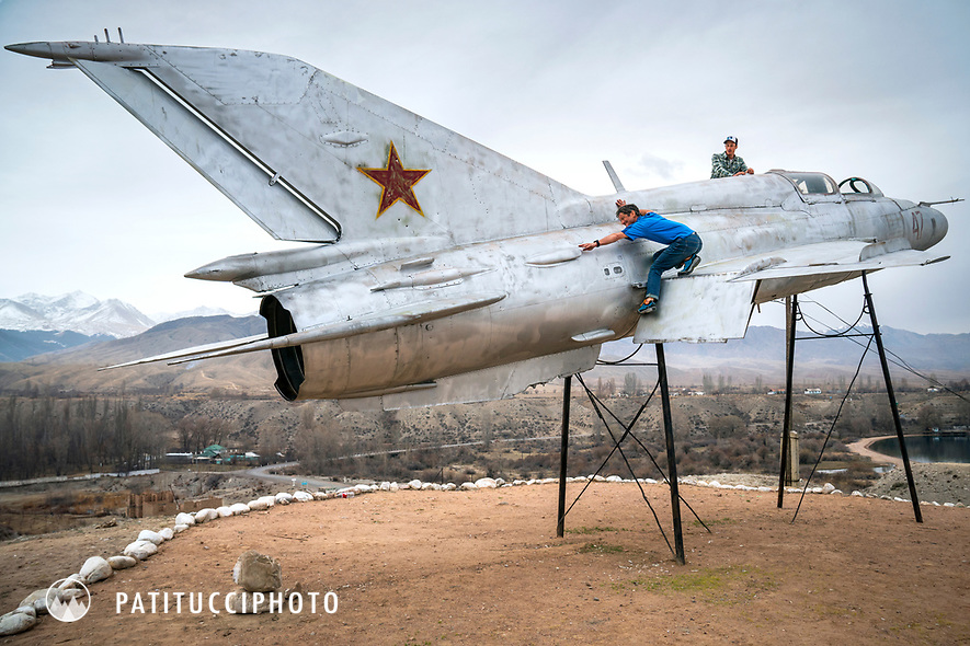 Two men playfully pose on a military jet display, Kyrgyzstan