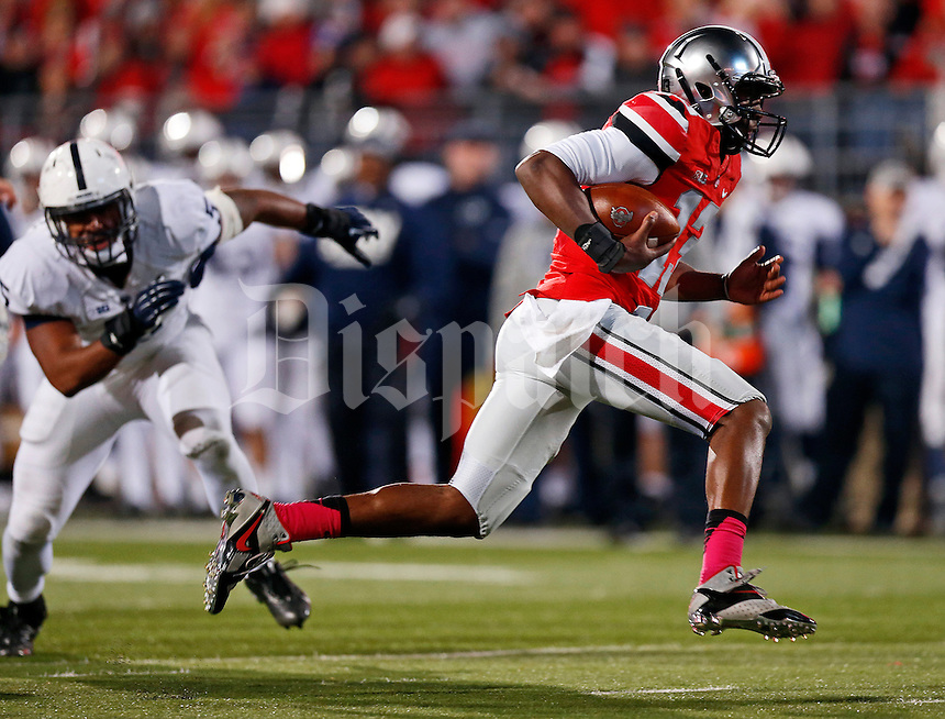 Ohio State Buckeyes quarterback Kenny Guiton (13) rushes for a touchdown past Penn State Nittany Lions linebacker Nyeem Wartman (5) during the fourth quarter of the NCAA football game at Ohio Stadium in Columbus on Oct. 26, 2013. (Adam Cairns / The Columbus Dispatch)