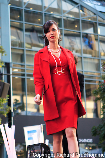 Frank Lyman fashion show held during the Montreal Fashion & Design festival in downtown Montreal.   Model is wearing a red dress and matching 3/4 length red coat