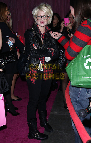 """KELLY OSBOURNE .Attending the Launch of The """"Tarina Tarantino Beauty"""" Cosmetic Collection presented Exclusively at Sephora,.Hollywood, California, USA,.24th February 2010..full length glasses geek frames black Chanel bag leather jacket red plaid shirt white top mouth open interview gingham check checked .CAP/ADM/KB.©Kevan Brooks/AdMedia/Capital Pictures."""
