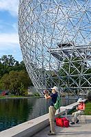 Senior tourist taking a photograph outside the Montreal Biosphere in Parc Jean Drapeau, Ile Sainte-Helene, Montreal, Quebec, Canada