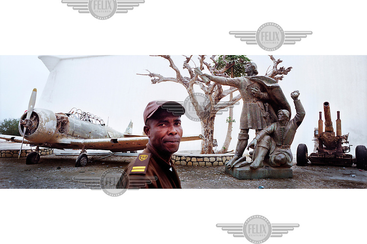 A security guard walks past an old propeller fighter plane, a howitzer and a statue outside the Fortaleza, a colonial fort. /Felix Features