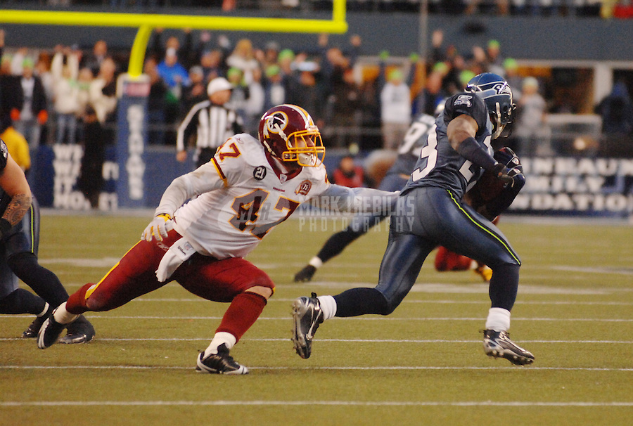 Jan. 5, 2008; Seattle, WA, USA; Seattle Seahawks cornerback Marcus Trufant (23) breaks the tackle of Washington Redskins tight end Chris Cooley (47) on his way to a fourth quarter interception for a touchdown during the NFC wild card game at Qwest Field. Seattle defeated Washington 35-14. Mandatory Credit: Mark J. Rebilas-US PRESSWIRE