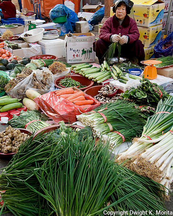 A woman prepares her vegetables for sale in a market stall found in Wonju, Korea