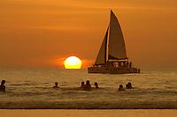 surfers off beach with sailboat, catamaran, Tamarindo beach Sunset Costa Rica, Pacific Ocean