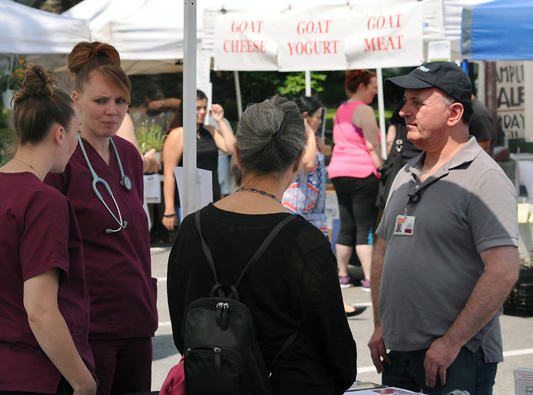 Members of the Colon Health booth meeting with, Gerry Harrington, who coordinated the Health Alliance Group's participation in Health Day theme, at the Saugerties Farmer's Market on Main Street in the Village of Saugerties, NY, on Saturday, June 10, 2017. Photo by Jim Peppler. Copyright/Jim Peppler-2017.