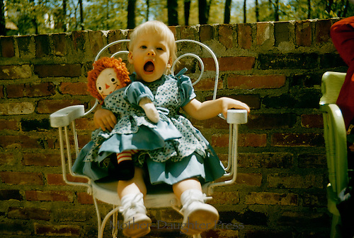 Young girl with mouth wide open poses for picture - holding doll with matching dress
