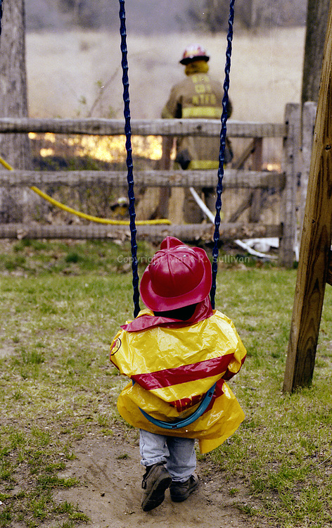 4/25/96<br /> 3 yr old Austin Andersen sits in his firemens outfit as real firefighters work on putting out a brush fire behind his Middetown home.