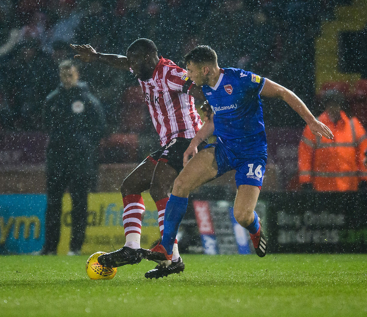 Lincoln City's John Akinde vies for possession with Morecambe's Sam Lavelle<br /> <br /> Photographer Chris Vaughan/CameraSport<br /> <br /> The EFL Sky Bet League Two - Saturday 15th December 2018 - Lincoln City v Morecambe - Sincil Bank - Lincoln<br /> <br /> World Copyright © 2018 CameraSport. All rights reserved. 43 Linden Ave. Countesthorpe. Leicester. England. LE8 5PG - Tel: +44 (0) 116 277 4147 - admin@camerasport.com - www.camerasport.com