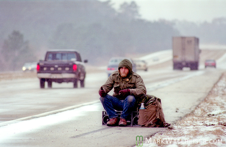 The dawn arrives to find a hitch hiker waiting on the side of I-10 covered with snow and ice two days before Christmas 1989 in Tallahassee, Florida.  The December 23rd snow accumulated enough to cause traffic issues and build snow men.